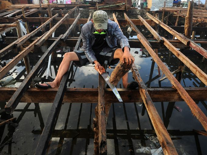 A man rebuilds his home which was destroyed by Typhoon Haiyan on a bay on Nov. 27 in Tacloban, Philippines (Photo: Noel Celis, AFP/Getty Images
